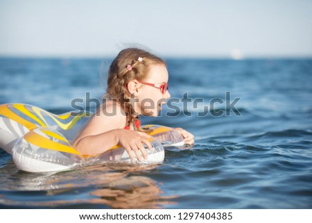 young girl in red glasses and a green bathing suit resting on the sea. childhood and sea air #1297404385
