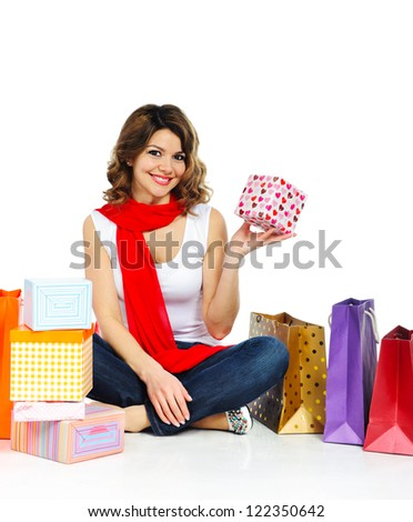 Young girl in red scarf sitting on floor with shopping bags isolated on white background