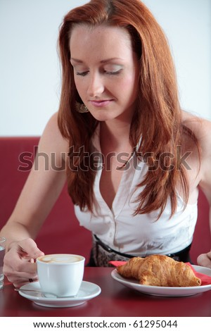 Young girl in restaurant in having coffee and croissant