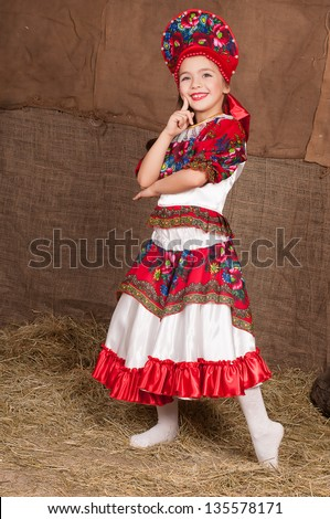 young girl in Russian national costume dancing to the music