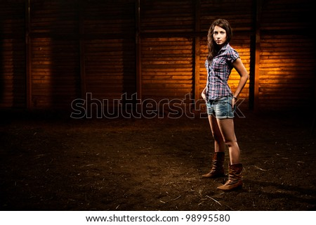 Young girl in shorts standing in the stable - stock photo
