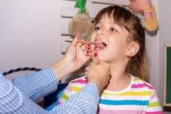 Young girl  in speech therapy office. Preschooler exercising correct pronunciation with speech therapist