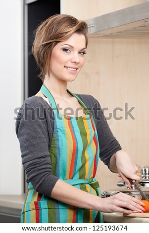 Young girl in striped apron cooks vegetables in the modern comfortable kitchen