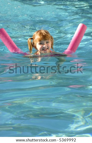 Young girl in swimming pool swimming with floating device