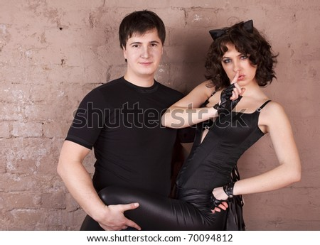 Young girl in the costume of cat woman flirting with the guy
