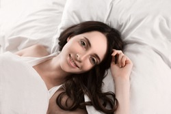 Young girl in the morning,lying in bed sleeping after hard work day tired.Nude makeup. Warm toning image.Fresh bedclothes,furnishing shop,new day, weekend,washing or laundry concept.