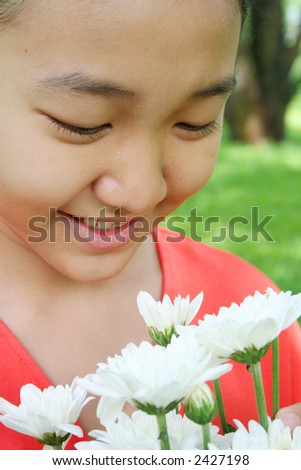 Young girl in the park with flowers.