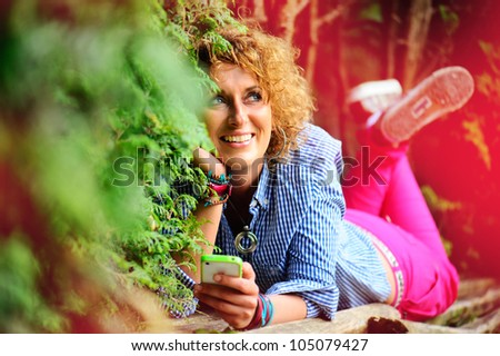 Young girl in the park with mobile phone.
