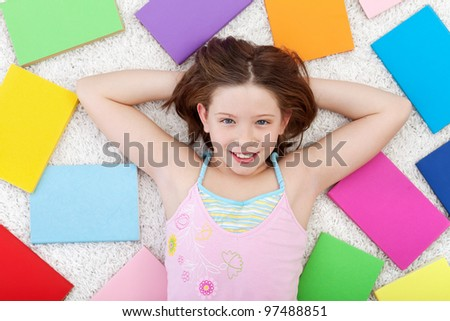 Young girl in the world books - on the floor smiling