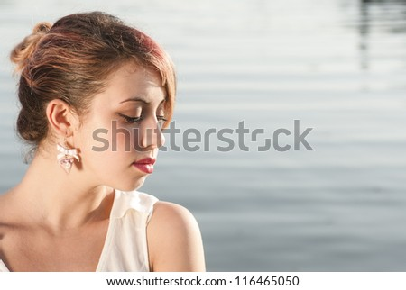 young girl in thoughtful exspression near the sea