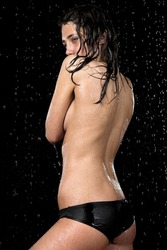 Young girl in underwear in rain isolated on black background