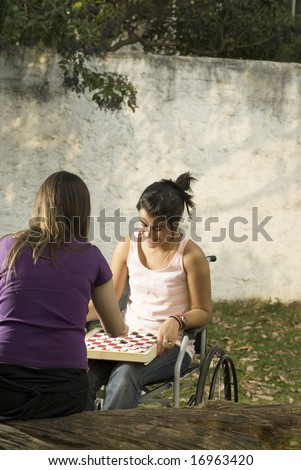 Young girl in wheelchair playing cards in with another girl. Vertically framed photo.