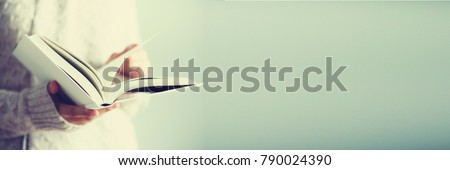 Young girl in white cardigan reading opened book. Copy space. lifestyle and school concept. Banner. #790024390