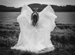 Young girl in white wedding dress standing in barley field. Looks like an angel. Black and white.