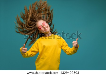 young girl in yellow clothes on blue background,concept of happiness,Portrait of pretty young woman in red sunglasses heart shape smiling, develop hair, blue background #1329402803
