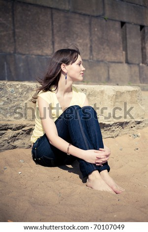Young girl in yellow on the sand