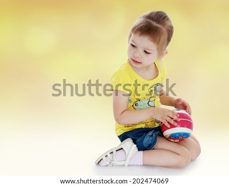 young girl in yellow shirt and ball in his hands.ball game,active lifestyle,happiness concept,carefree childhood concept.