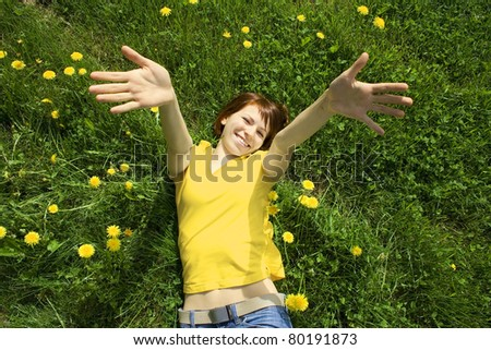 young girl in yellow shirt lying on grass, smiling and stretching her hands to camera - stock photo