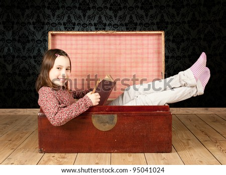 young girl inside an ancient trunk reading a book with a vintage background