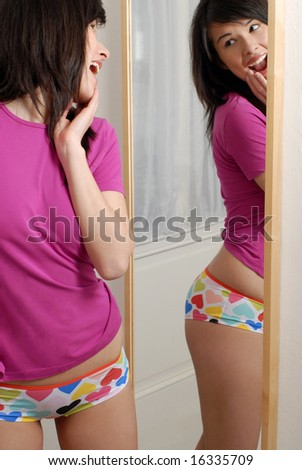 young girl is checking her body in front of a big mirror