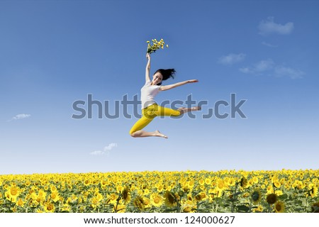 Young girl is dancing over yellow sunflowers
