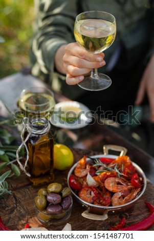 Young girl is holding a glass of white wine in her hand. Delicious italian food on the table: fried spicy shrimps in copper pan, olive oil, bread, olives. Light healthy meal, tasty snack #1541487701
