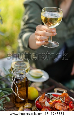 Young girl is holding a glass of white wine in her hand. Delicious italian food on the table: fried spicy shrimps in copper pan, olive oil, bread, olives. Light healthy meal, tasty snack #1541965331