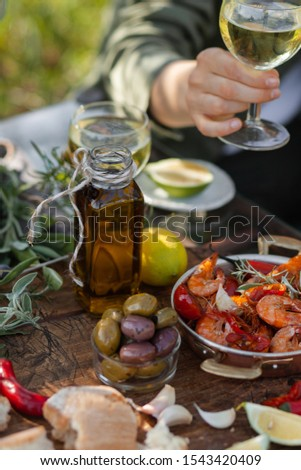 Young girl is holding a glass of white wine in her hand. Delicious italian food on the table: fried spicy shrimps in copper pan, olive oil, bread, olives. Light healthy meal, tasty snack #1543420409
