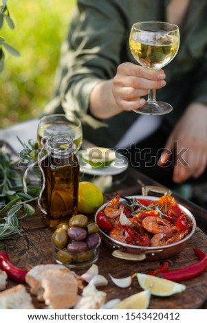 Young girl is holding a glass of white wine in her hand. Delicious italian food on the table: fried spicy shrimps in copper pan, olive oil, bread, olives. Light healthy meal, tasty snack #1543420412