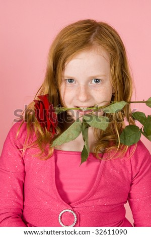 young girl is holding a red rose between her teeth on pink