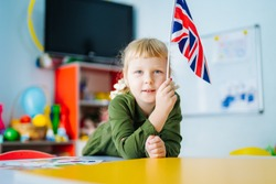 Young girl is holding Union Jack flag. British flag on the front view. Blurred background. Closeup.