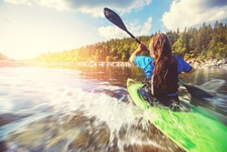 Young girl is kayaking with spray paddle splashes. Summer day, travel concept.