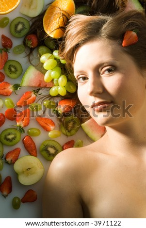 young girl is lying between many fruits