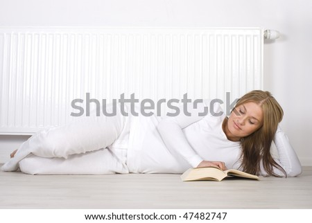 Young girl is lying by a white heater
