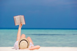 Young girl is reading a book lying on tropical white beach