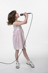 Young girl is recording her song in the studio. Singing little cutie holds black microphone in her hands on the same level with her opened mouth. Face in profile. White background in the studio.