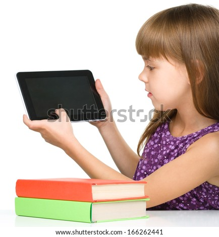 Young girl is showing tablet while sitting at table, isolated over white