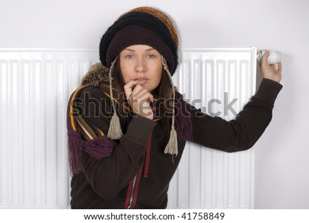 Young girl is standing by a white heater