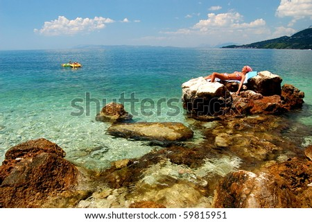 Young girl is sunbathing on rocky beach in Croatia