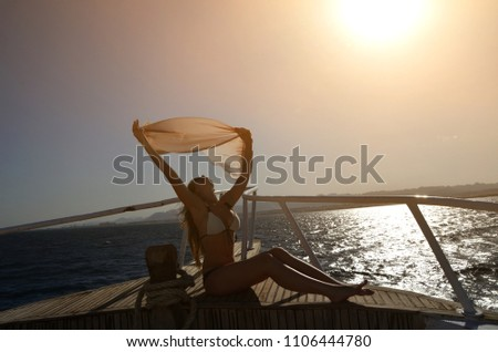 young girl is traveling on the sea in summer at sunset.