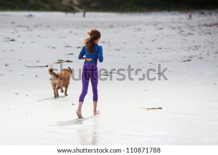 young girl jogs with a dog along the beach