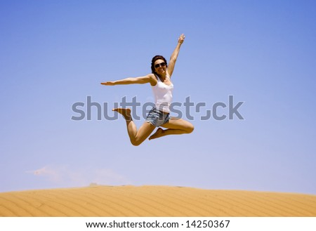 Young girl jump on the sand