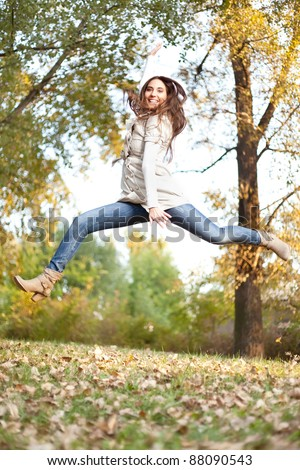 young girl jumping in autumn park, high jump