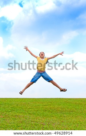 Young girl jumping in the air, over green field