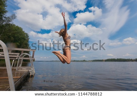 Young girl jumping into water, summer time - Shutterstock ID 1144788812