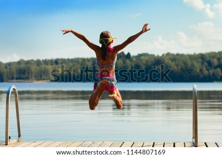 Young girl jumping into water, summer time - Shutterstock ID 1144807169