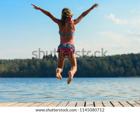 Young girl jumping into water, summer time - Shutterstock ID 1145080712