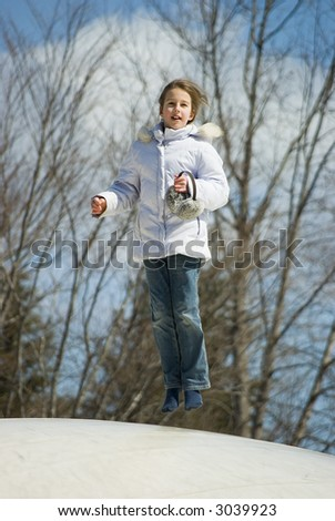 Young girl jumping on the trampoline