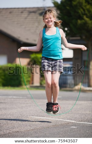 Young girl jumping rope outdoors