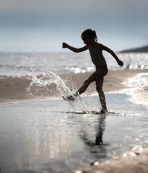 young girl kicks the water at the beach holiday